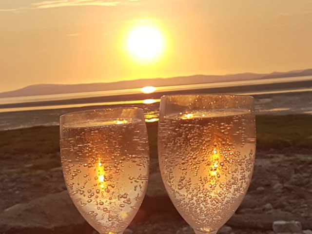 a sunset with champagne glasses in the foreground