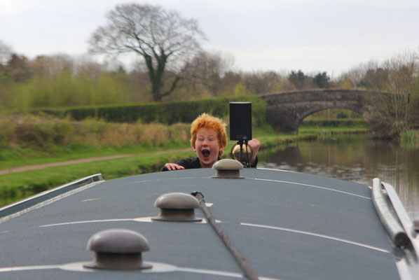 a child looks delighted as he stands at the helm of a narrowboat behind him is a bare tree and a stone bridge
