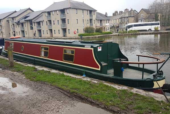 poppy the narrowboat moored in the rain near buildings