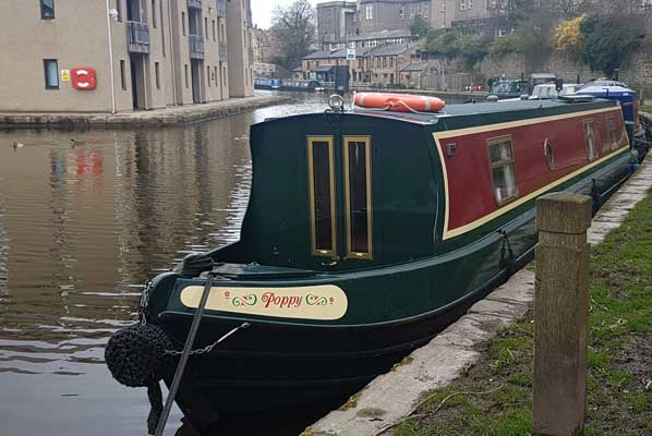 poppy the narrowboat moored on the lancaster canal in a small town