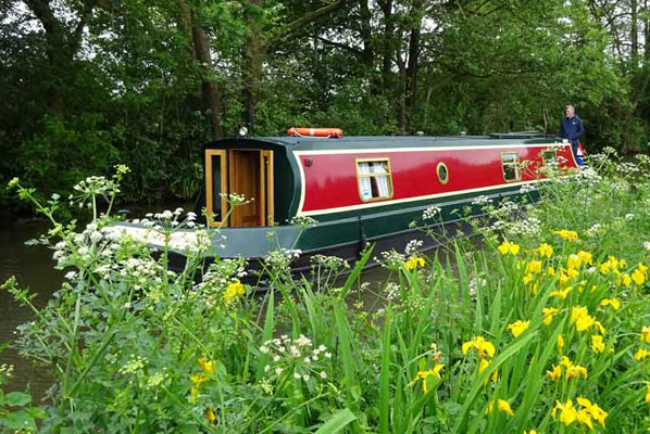 poppy the narrowboat piloted along the lancaster canal with spring flowers and daffodils