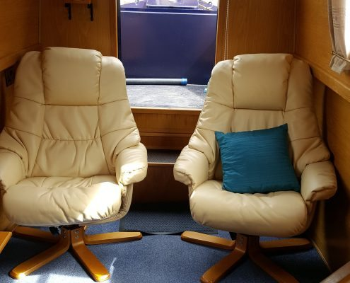 Two comfortable looking leather and wood chairs in the cabin of a narrowboat