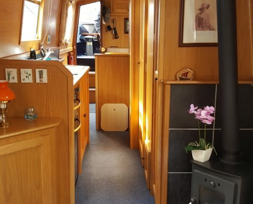 The cabin of a narrowboat is lit by sunlight, with bright blonde wood throughout and a wood burning stove in the foreground