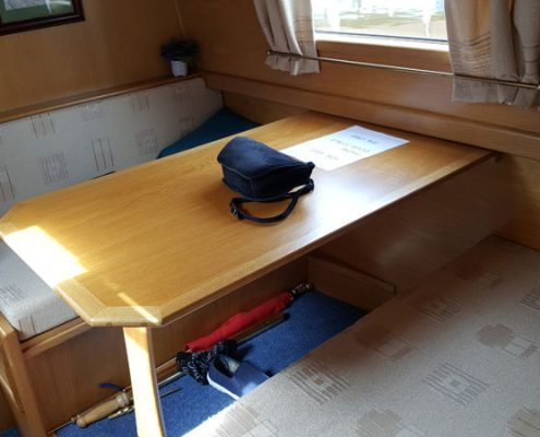 a bag sits on a table in the cabin of a narrowboat beneath the table are an umbrella and a single shoes