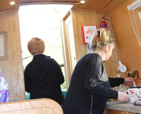 a woman makes cups of tea in the kitchen of a narrowboat while a second person looks from the cabin out over the lancaster canal