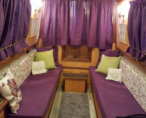 rose the narrowboat interior showing purple curtains and furnishing and light wood finish