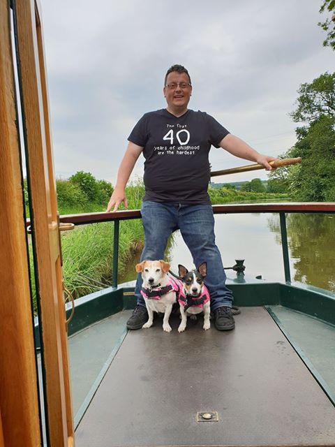 a man stands with two dogs in the stern of a narrowboat on the lancaster canal