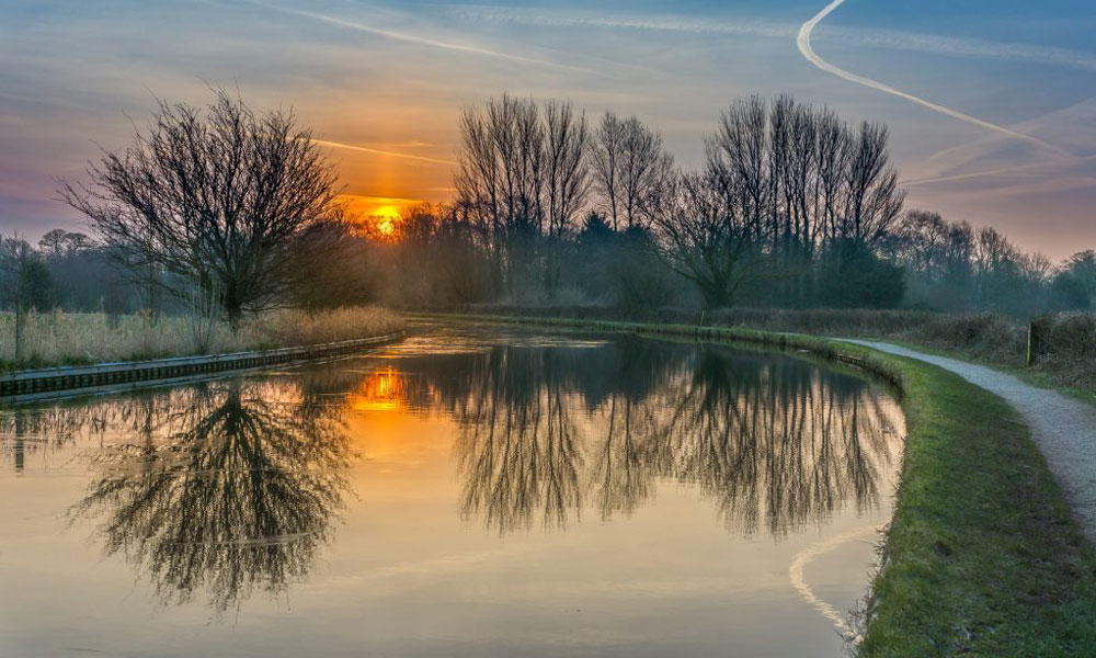 dawn on a cold lancaster morning showing the sunrise over a frosty canal with bare trees