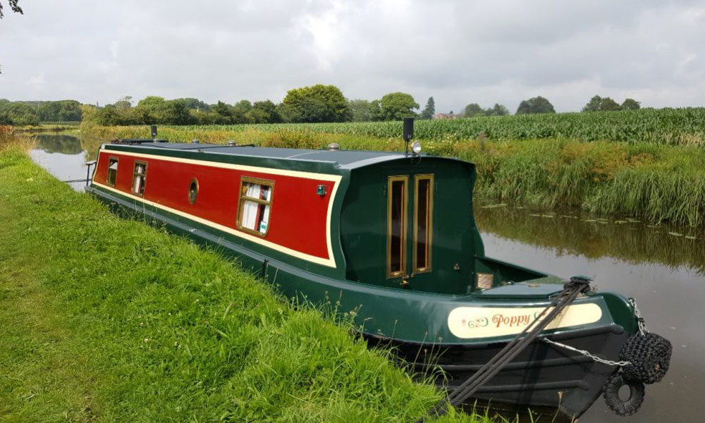 poppy the narrowboat moored on the lancaster canal beside open fields beneath a blue sky